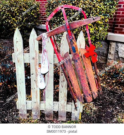 Old fashioned sled and ice skates hanging from picket fence section. Modern art
