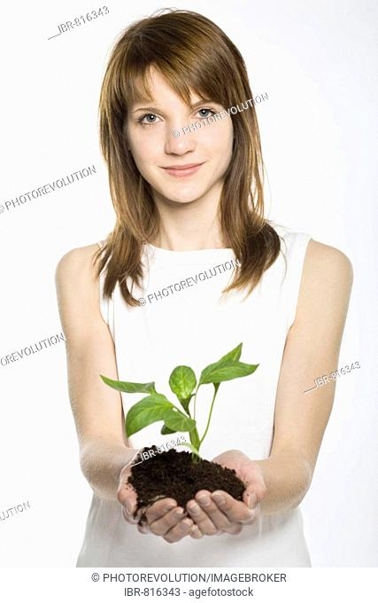 Young woman cupping a young plant rooted in soil in her hands