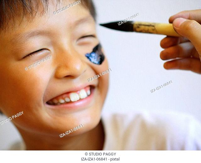 Close-up of a boy getting a face paint design on his face