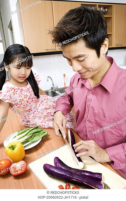 Close-up of a mid adult man and his daughter cutting vegetables at a kitchen counter
