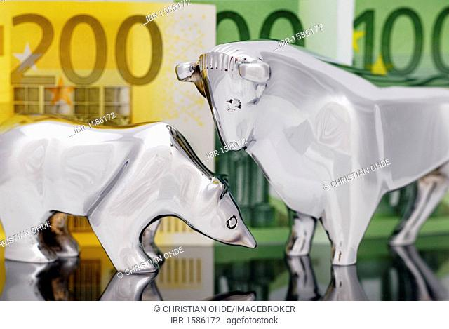 Stock market symbols bull and bear in front of euro banknotes, symbolic image for financial transaction tax