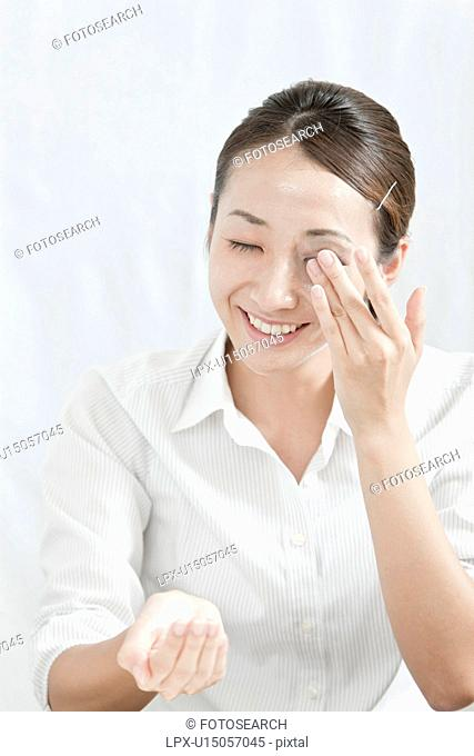 Young woman removing make-up, Tokyo Prefecture, Japan