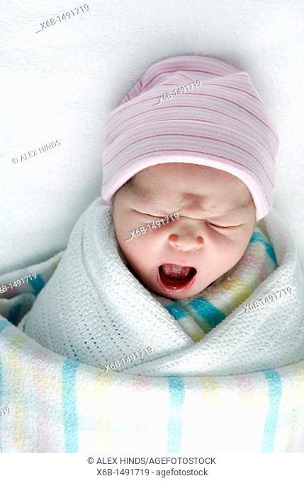A newborn baby swaddled in blankets