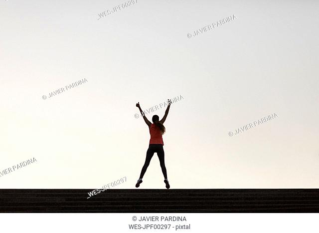 Rear view of successful sportswoman raising her arms