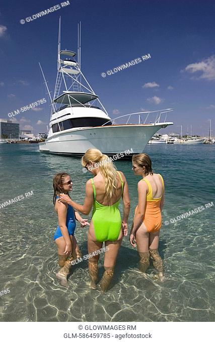 Rear view of a mature woman with her daughters standing in the sea