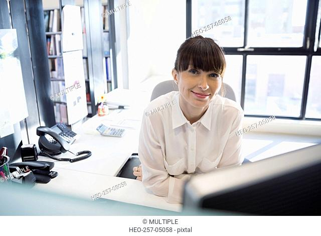 Portrait smiling businesswoman at desk in office