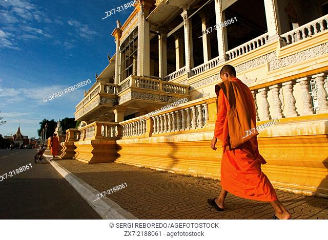Monks walk outside the Royal Palace. Phnom Penh. Gleaming in gold, the Royal Palace is one of Phnom Penh's most splendid architectural achievements