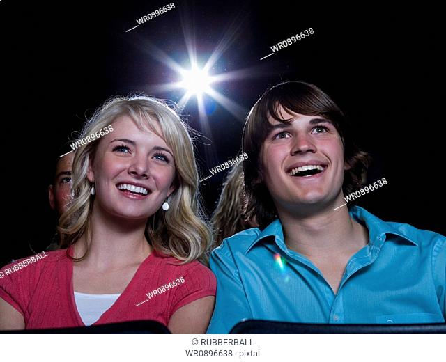 Boy and girl watching film at movie theater smiling