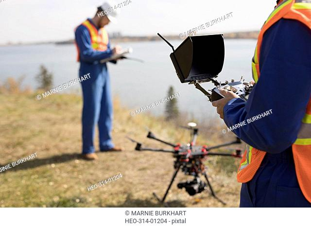 Surveyors with drone equipment at sunny lakeside