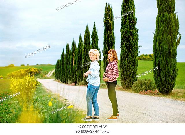 Two mature female friends on rural road, Tuscany, Italy
