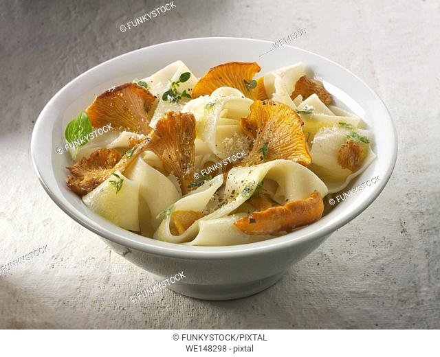 Wiild organic chanterelle or girolle Mushrooms (Cantharellus cibarius) or sauteed in butter and hebs with pappardelle pasta