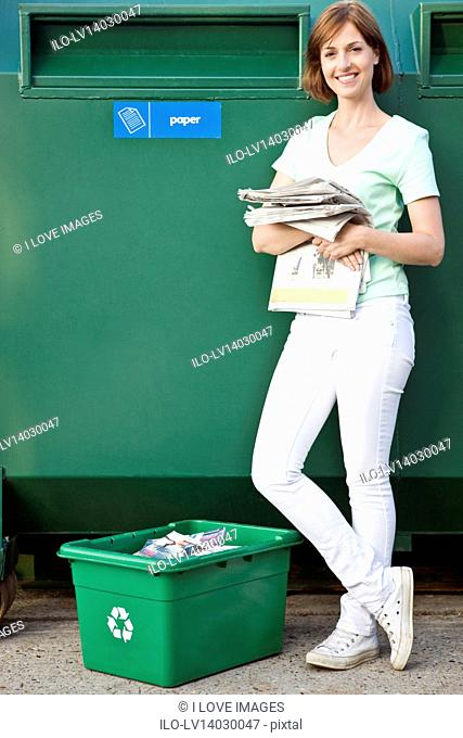 A mid-adult woman recycling paper