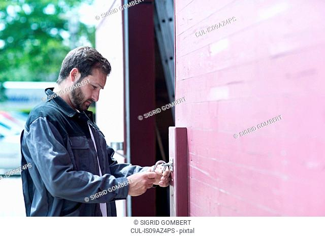 Man unlocking padlock on warehouse