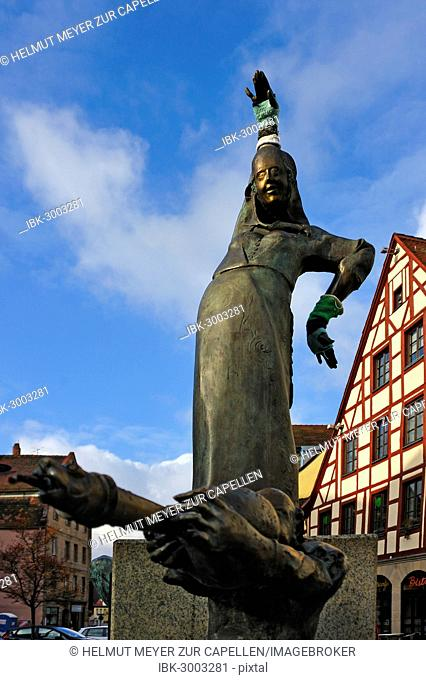 Statues wearing gloves on the Gauklerbrunnen well by artist Harro Frey, an old half-timbered house at the back, Gruener Markt square, historic district