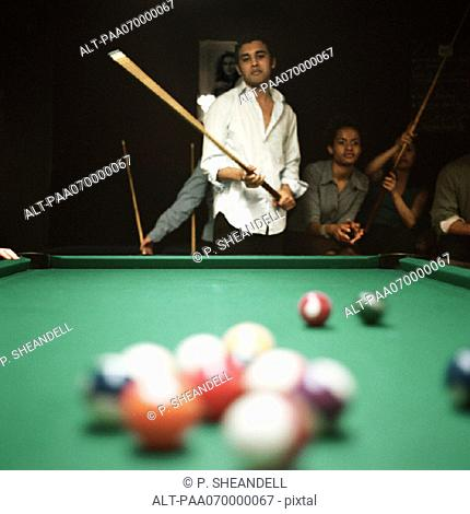 Young man shooting pool, people watching in background, billiard balls blurred in foreground
