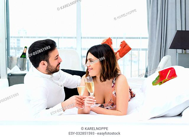 Close up portrait of young couple on honeymoon in hotel.Man and woman drinking champagne on bed in suite