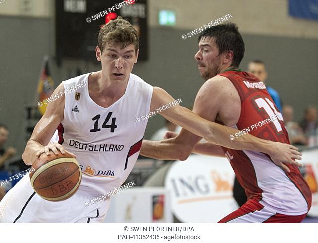 Germany's Andreas Seifferth (L) plays against Portugal's Miguel Miranda during the international basketball match Germany vs