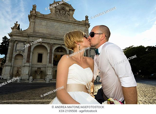 Newlyweds at the Gianicolo water fountain in Rome, Italy