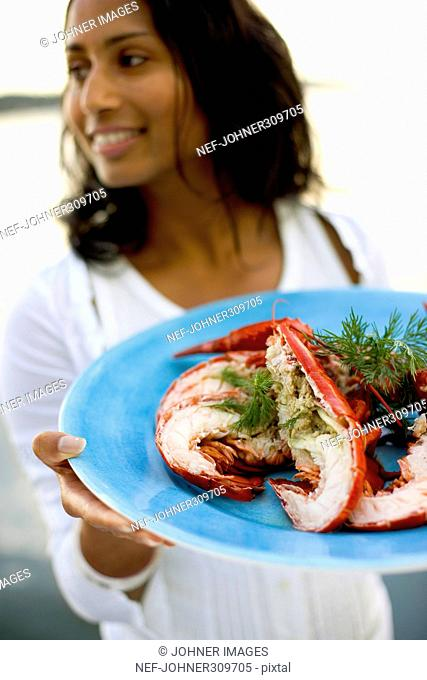 A woman serving lobster