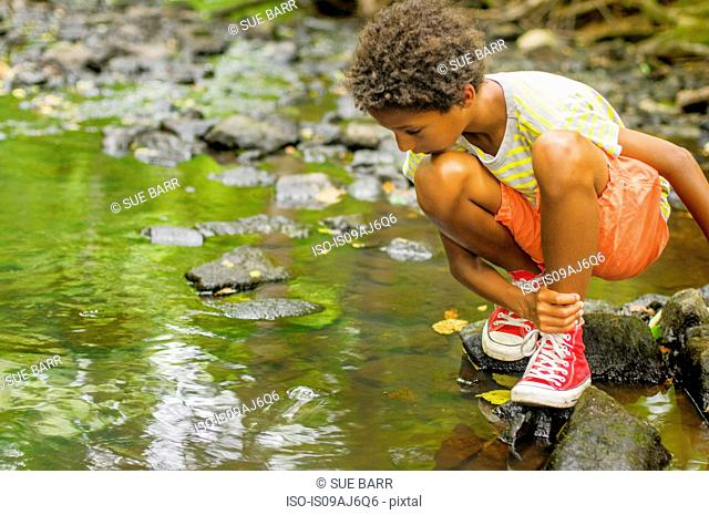 Boy looking for fish in river