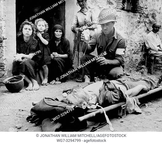 ITALY Sicily-- 09 Aug 1943 -- Private Roy Humphrey is being given blood plasma by Pfc Harvey White, after he was wounded by shrapnel