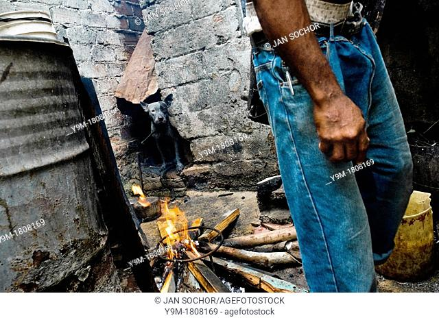 A Cuban man sets up the fire, required for a Palo religion ceremony, on the backyard of his house in Santiago de Cuba, Cuba, August 1
