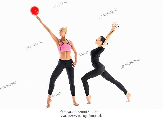 Elegant sports girl in black leggings. Perform gymnastic exercises with a ball. One stretched on tiptoes bend back and took in his hand the ball back
