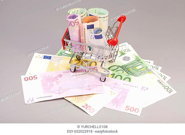 shopping cart full of euro banknotes isolated on gray background