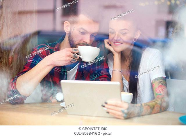 View through window of couple in coffee shop using digital tablet