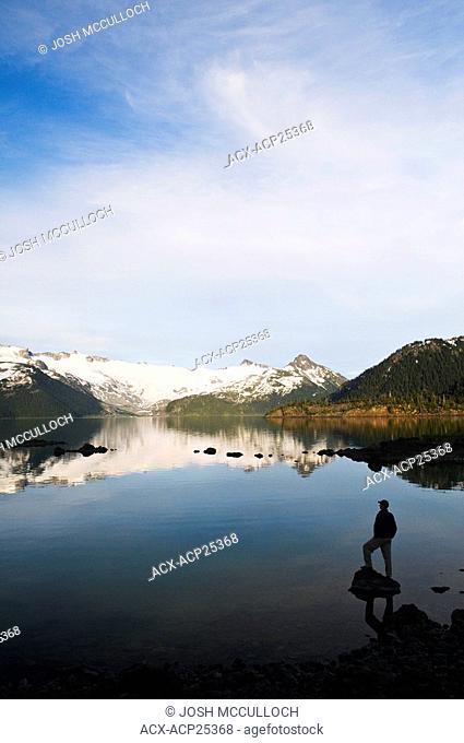 A hiker is silhouetted by the Sphinx Glacier and Garibaldi Lake in Garibaldi Provincial Park near Whistler BC