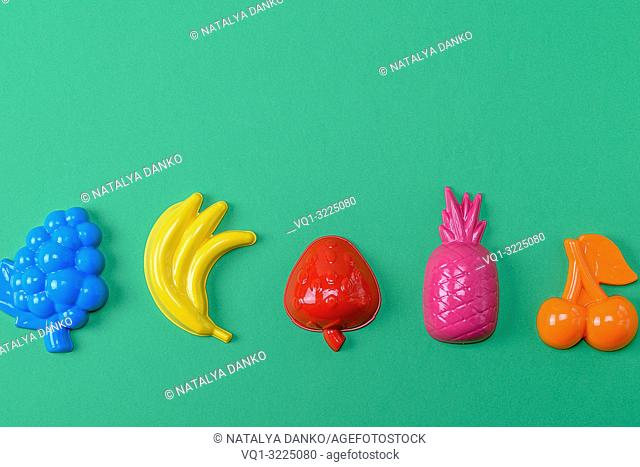 multicolored plastic toys fruits on a green background, copy space