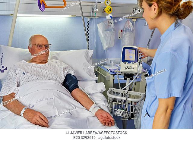 Nurse taking a patient's blood pressure, hospital room, Hospital Donostia, San Sebastian, Gipuzkoa, Basque Country, Spain