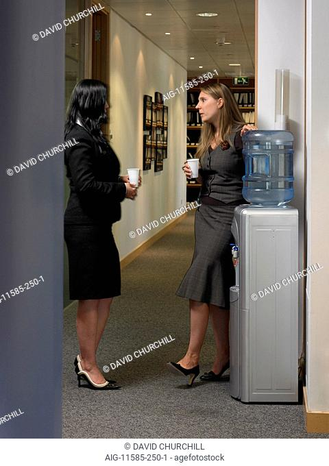 Office life and interiors (model released). Two female employees standing by water cooler drinking and conversing