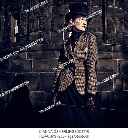 Female young adult in period clothing wearing black hat and veil with Harris tweed jacket and gloves holding riding crop