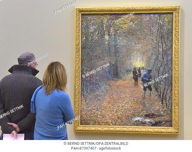 Visitors look at the painting 'The Hunt' by Claude Monet at the Museum Barberini in Potsdam, Germany, 21 January 2017. More than 1