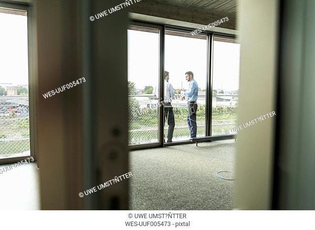 Two young businessmen standing on balcony talking