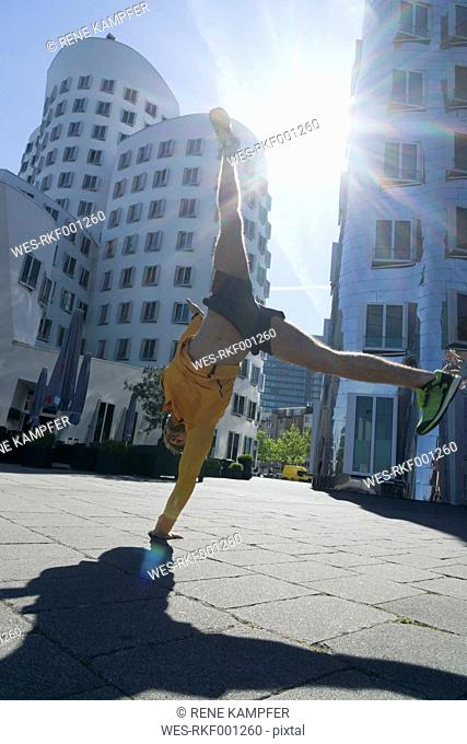 Germany, Duesseldorf, athlete doing a handstand at media harbor