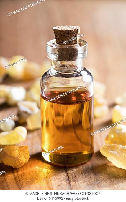 A transparent bottle of frankincense essential oil with frankincense resin