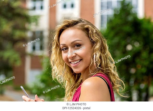 A beautiful young woman texting on her smart phone on a university campus and pausing to look at the camera; Edmonton, Alberta, Canada