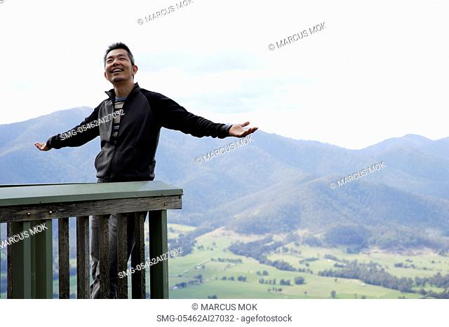 man smiling, standing on balcony with mountains as background