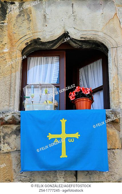 Window with Asturias flag and canary in a cage and flowers, in Llanes, Asturias, Spain