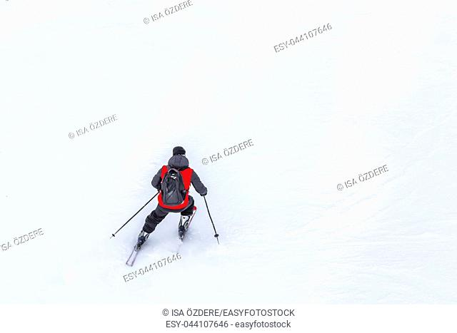 Man skier with red coat and black backpack skiing on fresh white snow on ski slope on Sunny winter day with Copy space in uludag mountain Bursa,Turkey