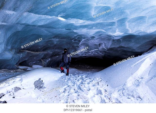 A man poses in front of a cave at the terminus of Fels Glacier (commonly misspelled Eel Glacier) in the Alaska Range in winter; Alaska, United States of America
