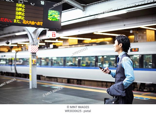 Businessman wearing blue shirt and vest standing on train station platform, holding mobile phone