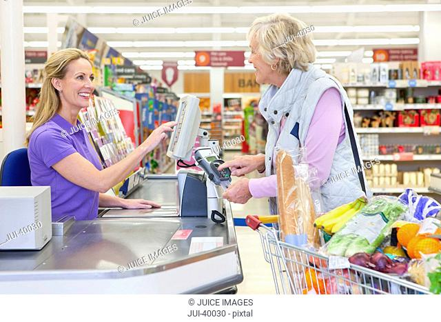 Cashier Serving Customer At Supermarket Checkout