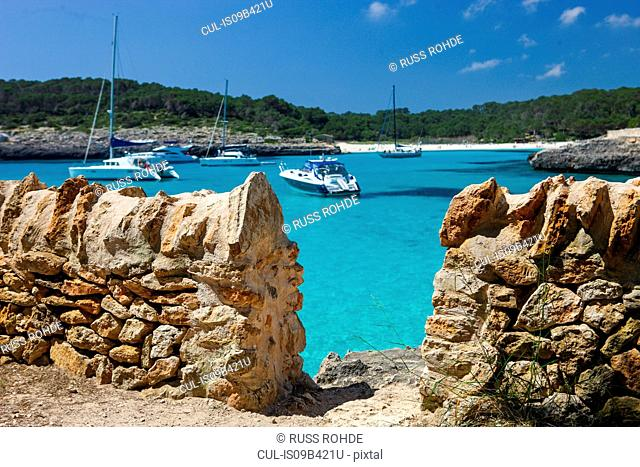 Traditional stone wall and anchored yachts in bay, Majorca, Spain