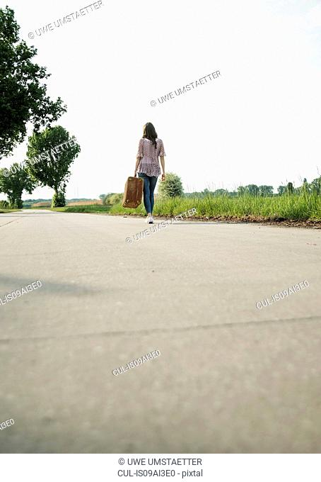 Young woman walking on country road carrying suitcase