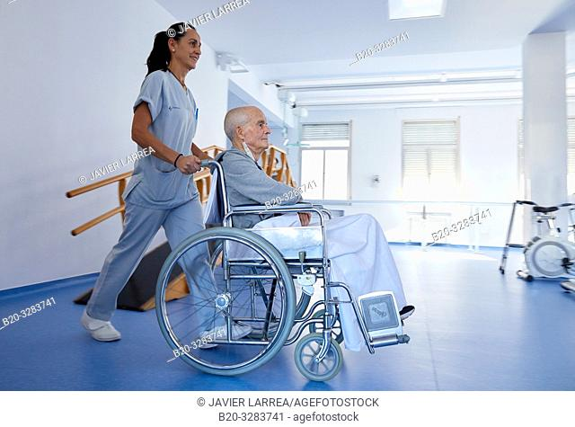 Keeper carrying a patient in a wheelchair, Rehabilitation, Hospital Donostia, San Sebastian, Gipuzkoa, Basque Country, Spain