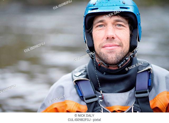 Portrait of mid adult male kayaker in watersports helmet