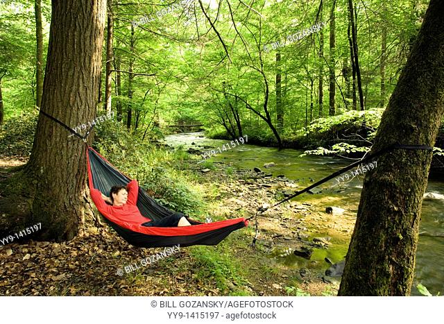 Woman relaxing in hammock by river - Pisgah National Forest - Brevard, North Carolina